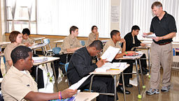 US_Navy_101110-N-0437M-397_Mooseheart_High_School_science_teacher_Curt_Schlinkman_hands_out_homework_to_his_students_who_are_also_Navy_Junior_ROTC