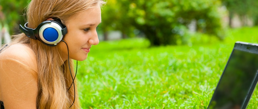 French A level Student listening to audio in the park