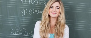 Female Maths student in front of blackboard with equations