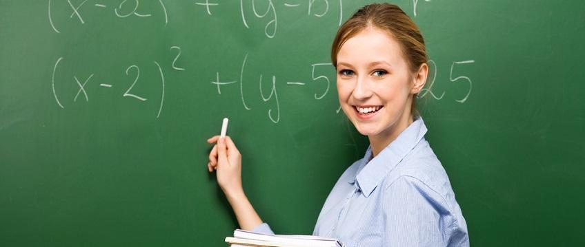 Student demonstrating Maths equations on blackboard